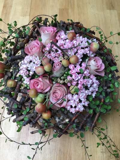 Hell lila Rosen im filigranen Holzkranz mit Apfelzweigen