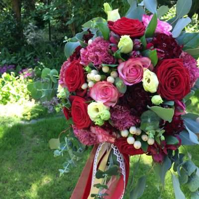 Brautstrauß aus bordeauxe farbenen Blüten mit creme Akzent